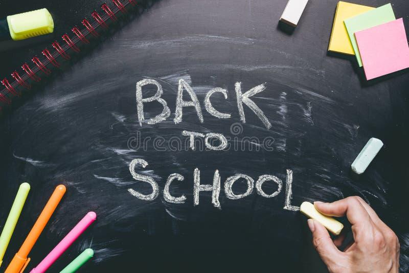 Hand som tillbaka skriver till skolan Skolatillförsel på svart tavlabakgrunden, utbildningsbegrepp royaltyfri fotografi
