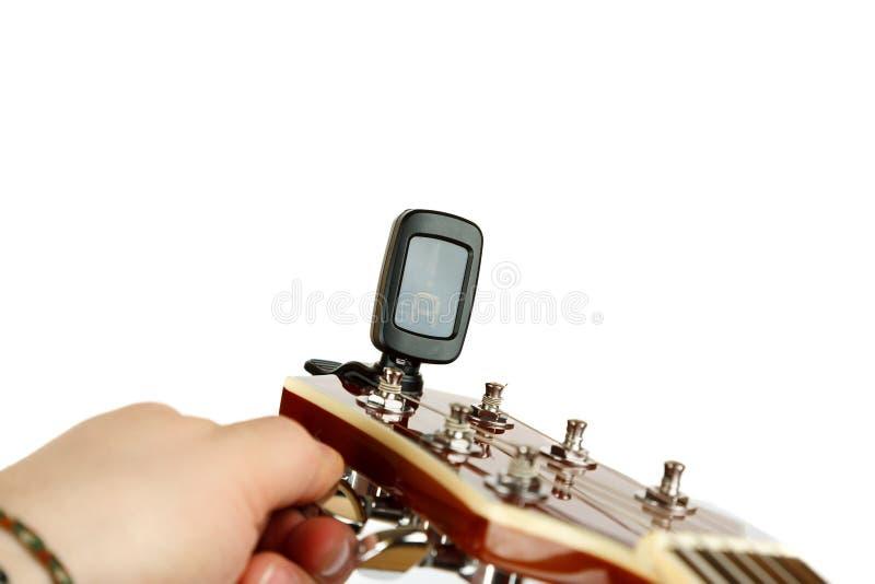 Hand som trimmar den akustiska gitarren med den elektroniska stämmaren arkivfoton