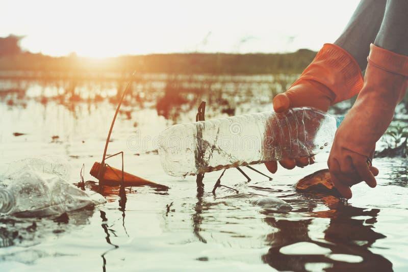 hand som upp väljer avskrädeplast- för att göra ren i floden royaltyfri bild