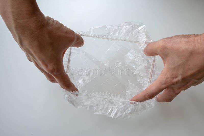 Hand som utvidgar den disponibla badmössan mot vit bakgrund arkivfoton