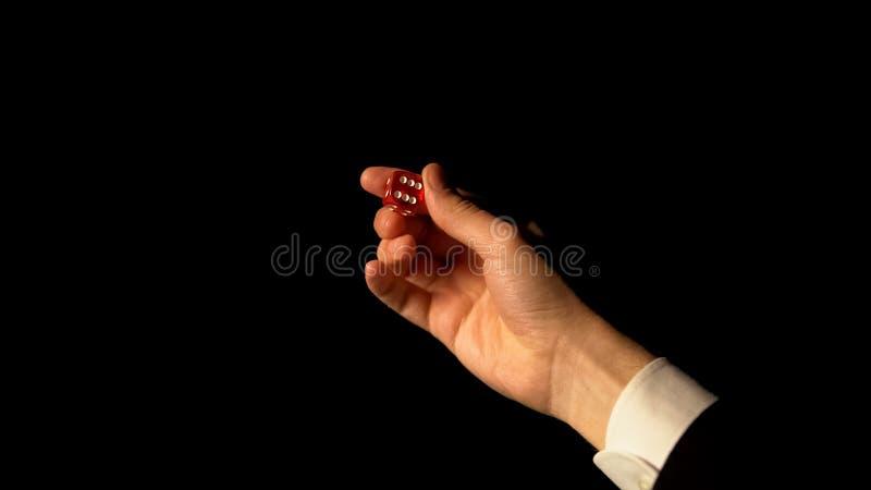 Hand som visar tärning mot svart bakgrund, risk och framgång, i att spela, kasino arkivfoton