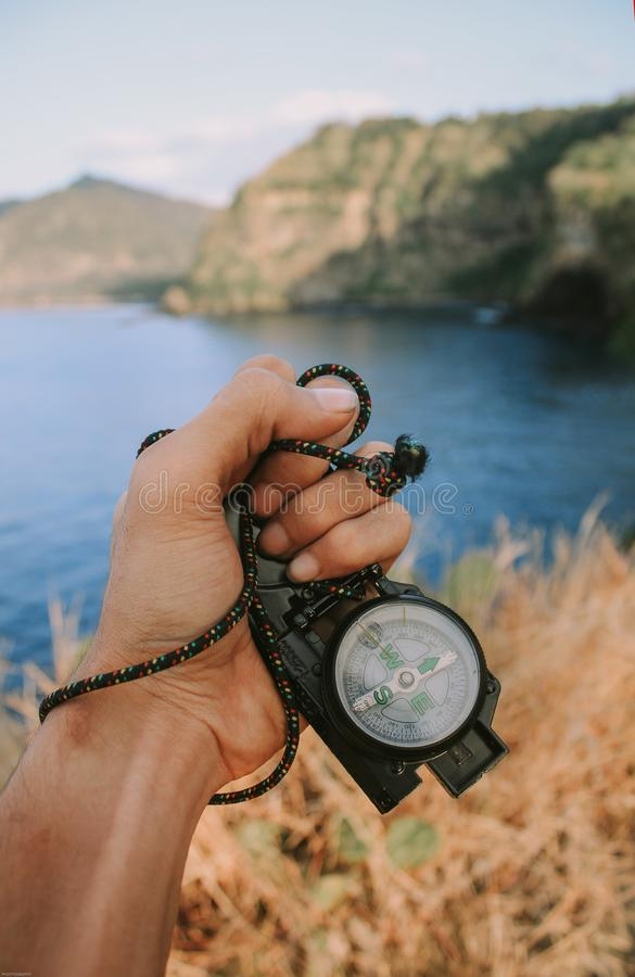 The hand of someone holding a compass, portraying an adventurer who is lost in the wild with a mountain and ocean background, and royalty free stock photography