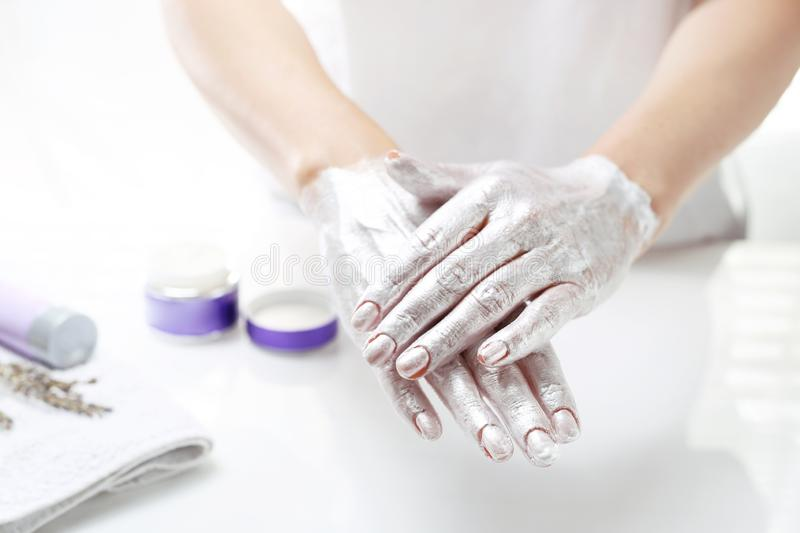 Hand spa. The woman puts a mask on the skin of the hand. Hand skin care royalty free stock photo