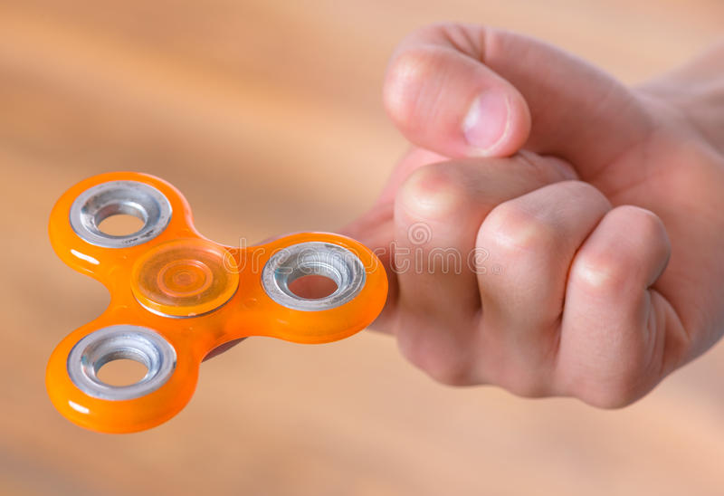 Hand with spinner toy. Male child hand holding popular fidget spinner toy - close up. Boy playing with a orange Spinner royalty free stock images