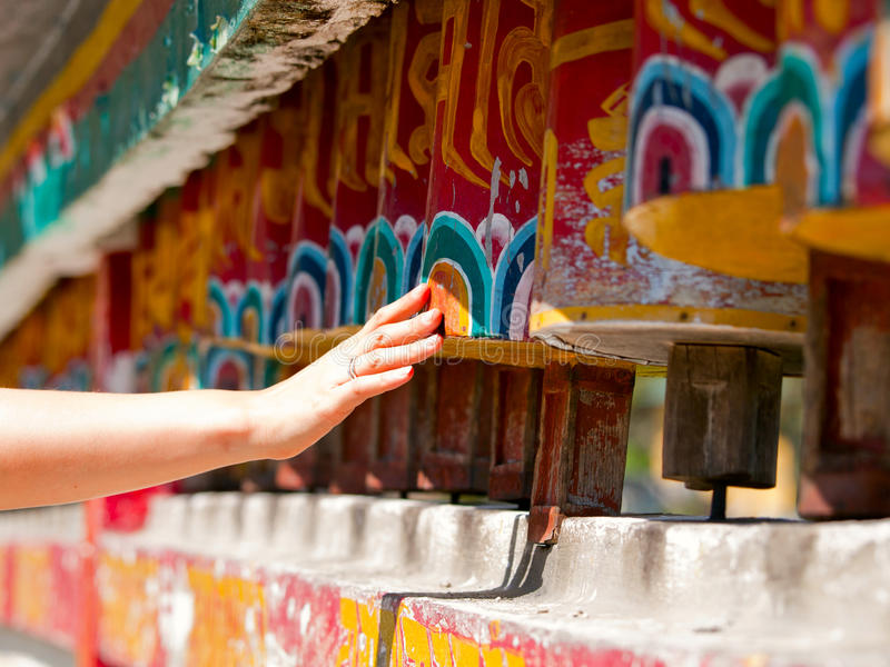 Hand spinning the prayer wheels royalty free stock photography