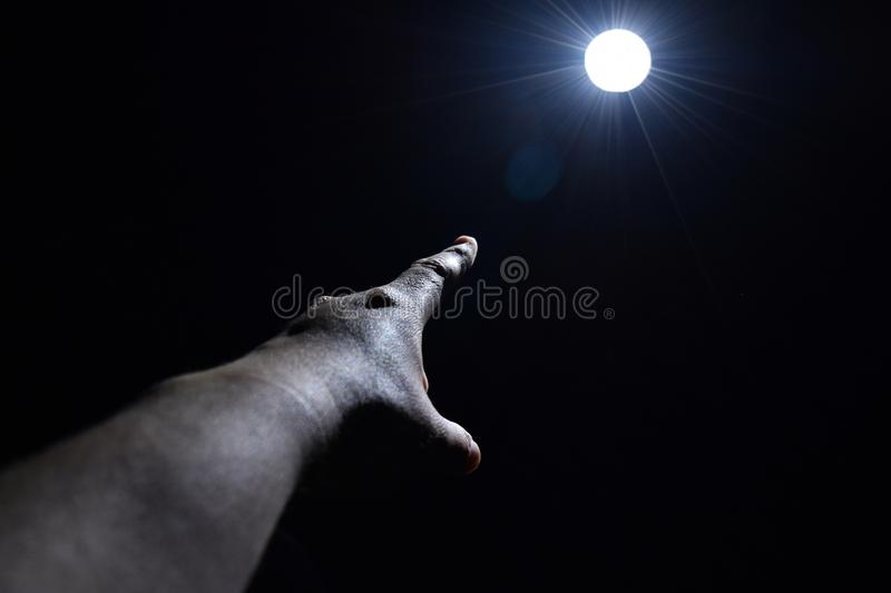 Hand and spot light in darkness royalty free stock image