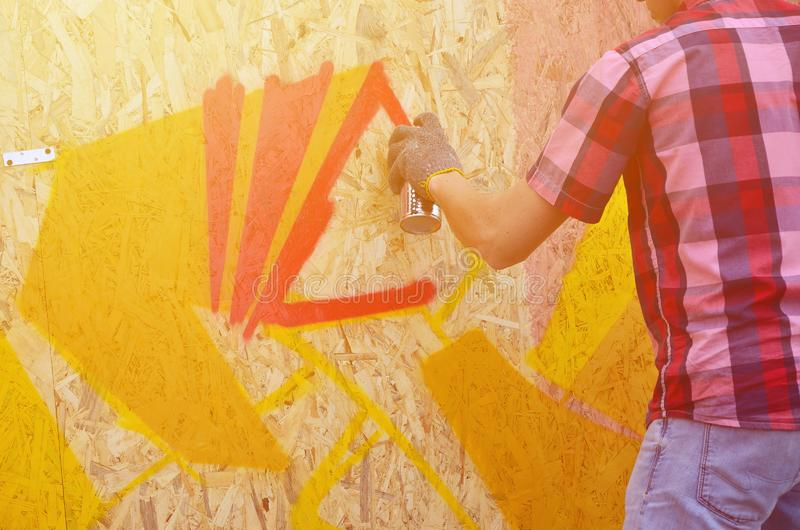 A hand with a spray can that draws a new graffiti on the wall. P. Hoto of the process of drawing a graffiti on a wooden wall close-up. The concept of street art stock photo