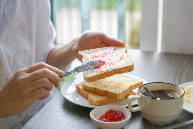 Hand spreading strawberry jam on toast stock images