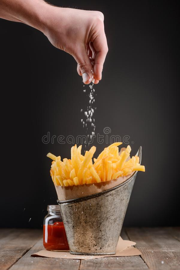 Hand sprinkles salt. On French fries. Whole bucket of fresh hot chips and jar of ketchup on wooden rustic table. Yummy royalty free stock image