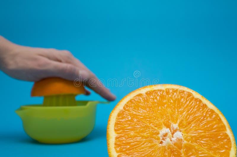 Hand squeezing orange on blue background stock images