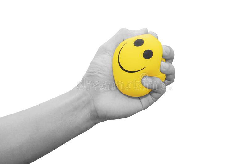 Hand squeezing smiling face yellow stress ball, isolated on white background stock photography