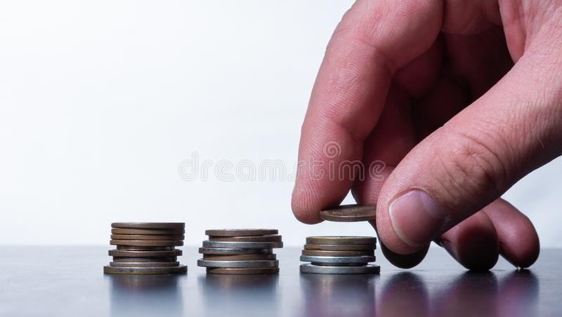 Hand stacking small coins on  a table stock photography