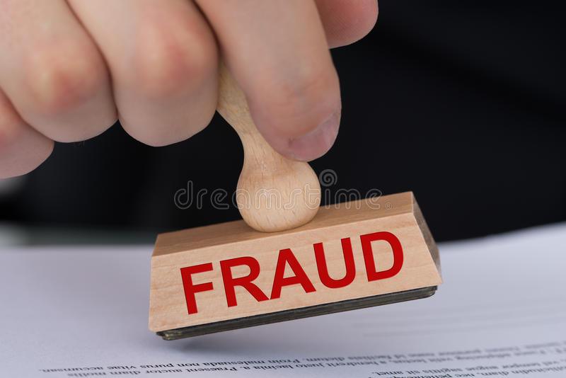 Hand Stamping Document With Fraud Rubber Stamp. Closeup of hand stamping document with Fraud rubber stamp at table in office royalty free stock photography