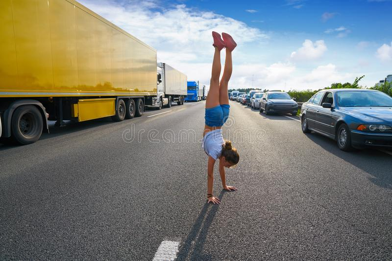 Hand stand girl in a traffic jam road stock photo