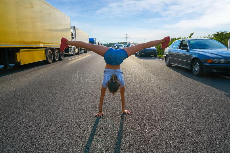 Hand stand girl in a traffic jam road royalty free stock photo