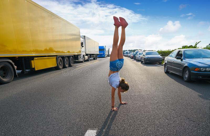 Hand stand girl in a traffic jam road stock images