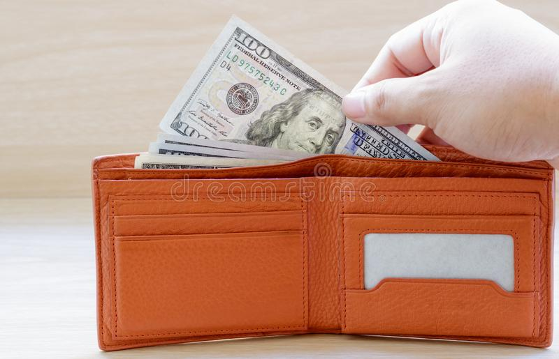 Hand stealing out money from wallet on wooden table. stock photos