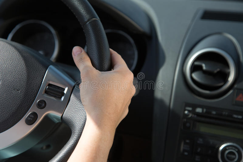 Hand on the steering wheel of a car royalty free stock images