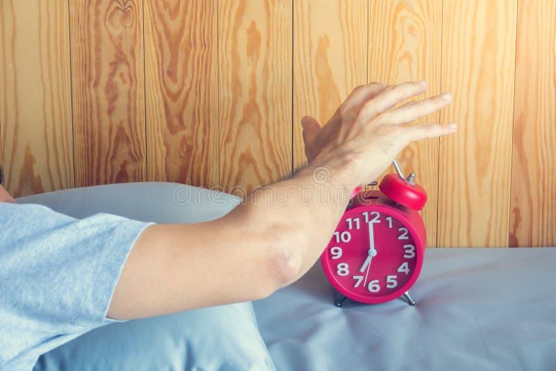 Hand stellt den Wecker ab, der am Morgen aufwacht Weiche Haut lizenzfreies stockfoto