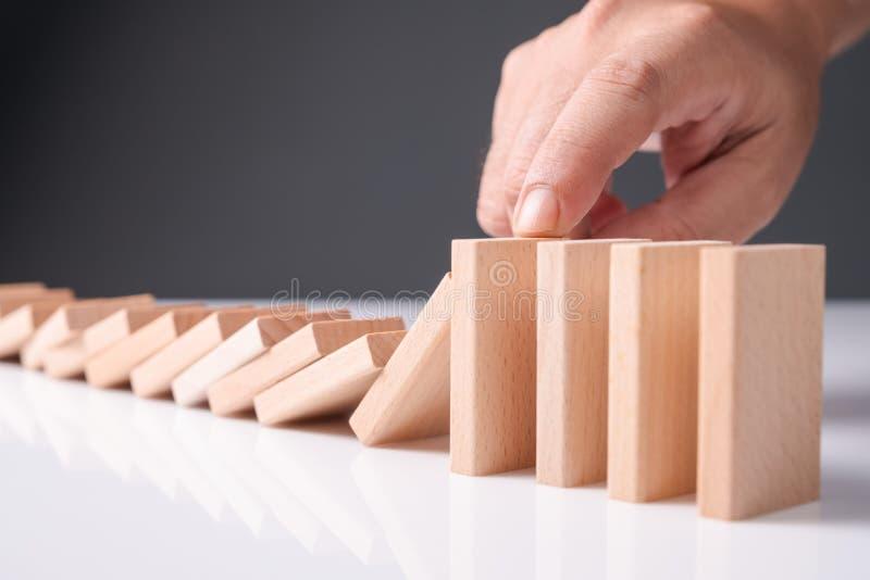 Hand Stop Falling Wood Domino royalty free stock photo