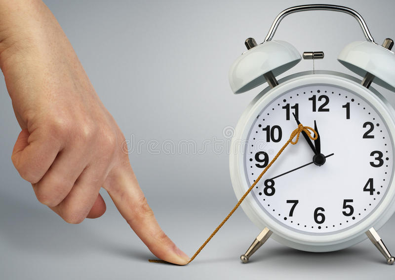 Hand stop time on alarm clock, deadline concept. Hand stop time on clock, deadline concept royalty free stock images