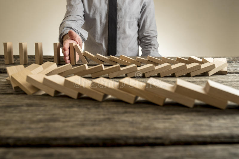 Hand stopping domino effect of wooden blocks. For concept about business and accountability royalty free stock photo