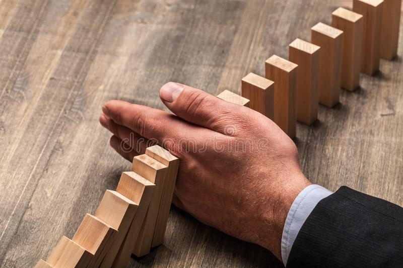 Hand stopping falling dominos, business concept stock image