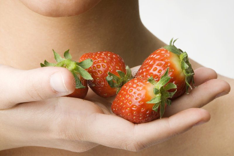 Hand and strawberry royalty free stock photography