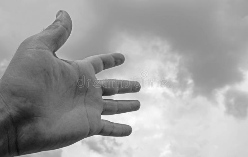 Hand stretched to a sky filled with dark clouds. suitable for book cover,card  illustration, presentation. Black and white stock photography
