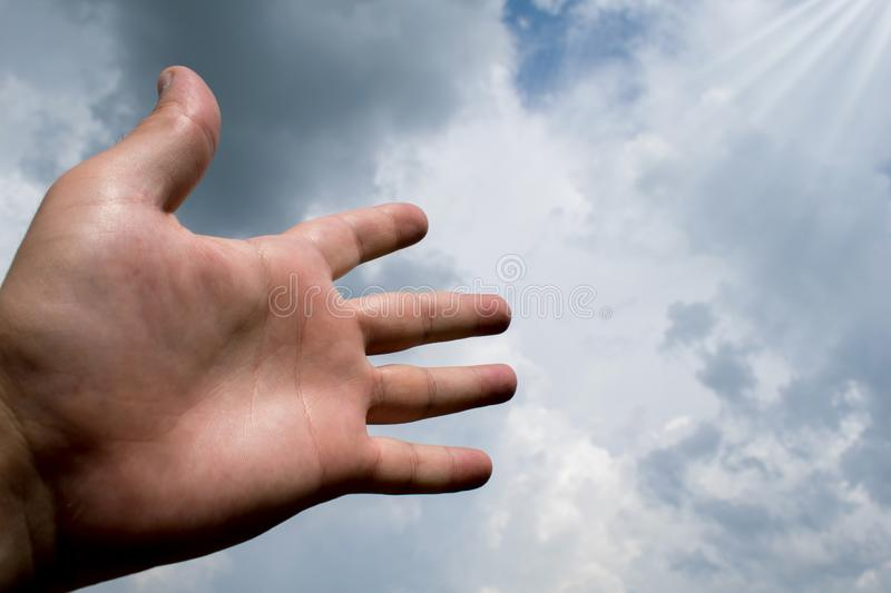 Hand stretched to a sky filled with dark clouds. suitable for book cover,card  illustration, presentation stock images