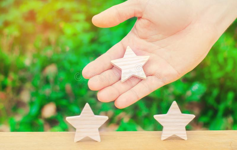 The hand stretches the third star to the other two. The concept of recognition of high quality and good service. Review hotel. Or cafe. High rating, success and royalty free stock photography