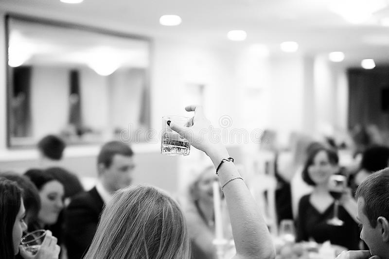 Hand of stylish woman holding glass of whiskey and toasting at l stock photography