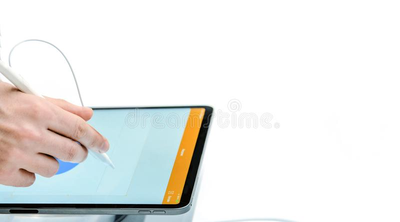 A hand with a stylus draws on a tablet. Digital technology. White isolated background. Close-up. stock photography