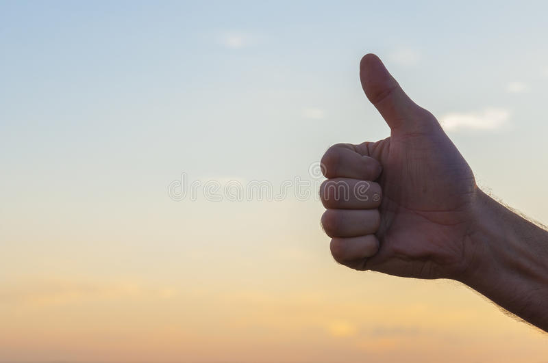 Hand at sunset sky background. OK sign royalty free stock images