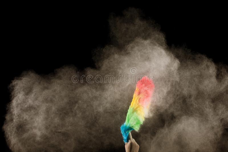 Hand sweeping dust clouds in the air.Housewives are dusting with plastic feathers stock photo