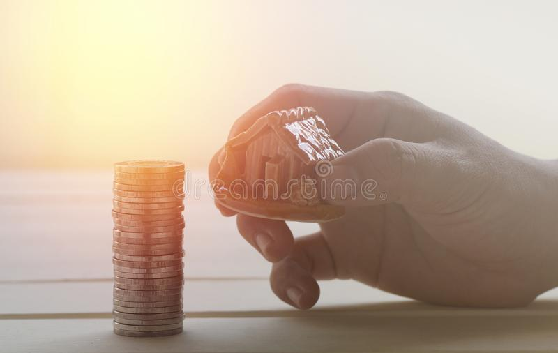 Hand take home on pile of money coin in loan concept photo and house finance stock photography