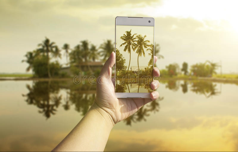 Hand taking photo of the fish village landscape stock photography