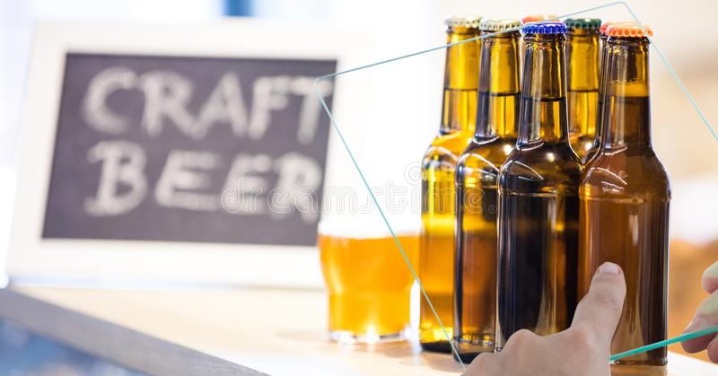 Hand taking picture of beer bottles through transparent device at bar stock images