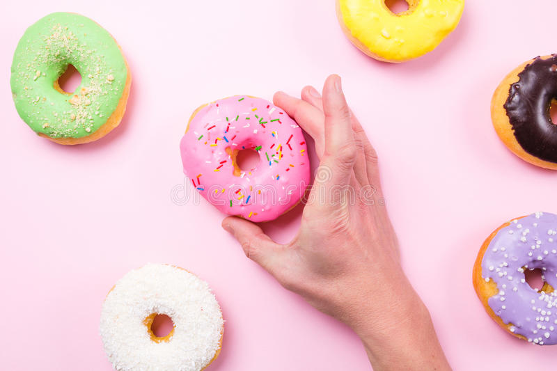 Download Hand Taking Pink Donut On Pastel Background Stock Photo - Image: 83718232