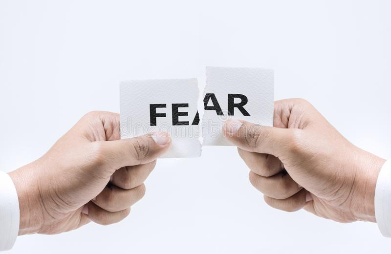 Hand tearing paper with FEAR word in white tone stock photo