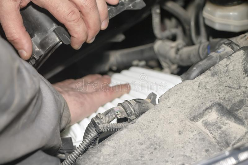 A hand technician checking or fixing the engine of a modern car. Replacement of the air filter royalty free stock photo