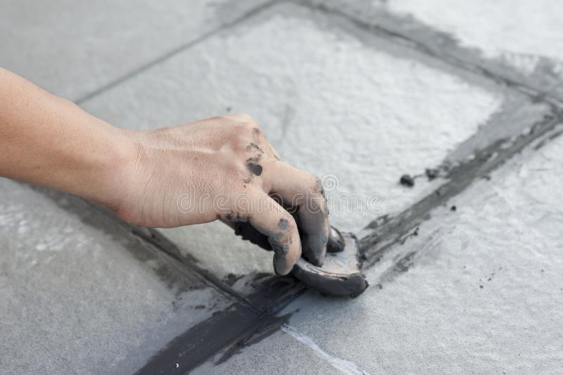 Hand of technician use of rubber flooring on gray color of new grout tile. Hand of technician use of rubber flooring on gray color of new grout tile on tile royalty free stock photography
