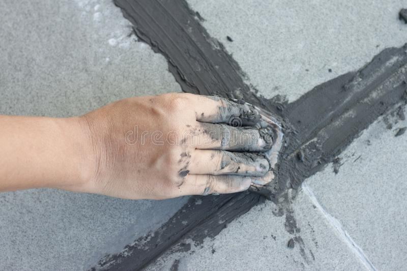 Hand of technician use of rubber flooring on gray color of new grout tile. stock photography