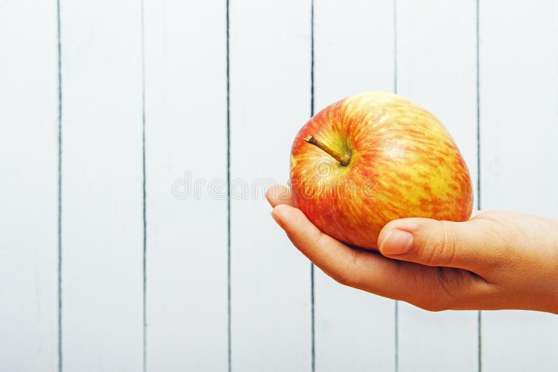 Hand of teenage girl with apple on wooden background with cpy space. Side view. Ecologic clean fresh fruit stock photos