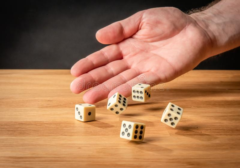 Hand throwing dice in front of a dark background royalty free stock images
