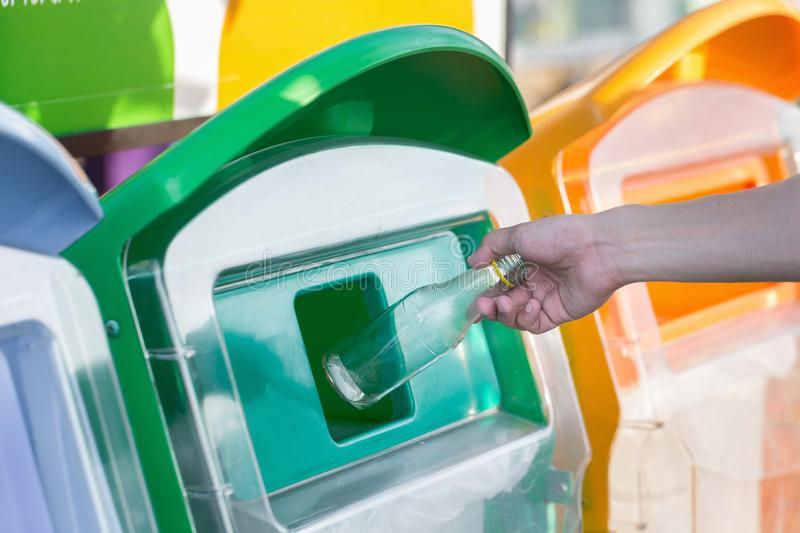 Hand throwing empty glass bottle into the trash stock photo