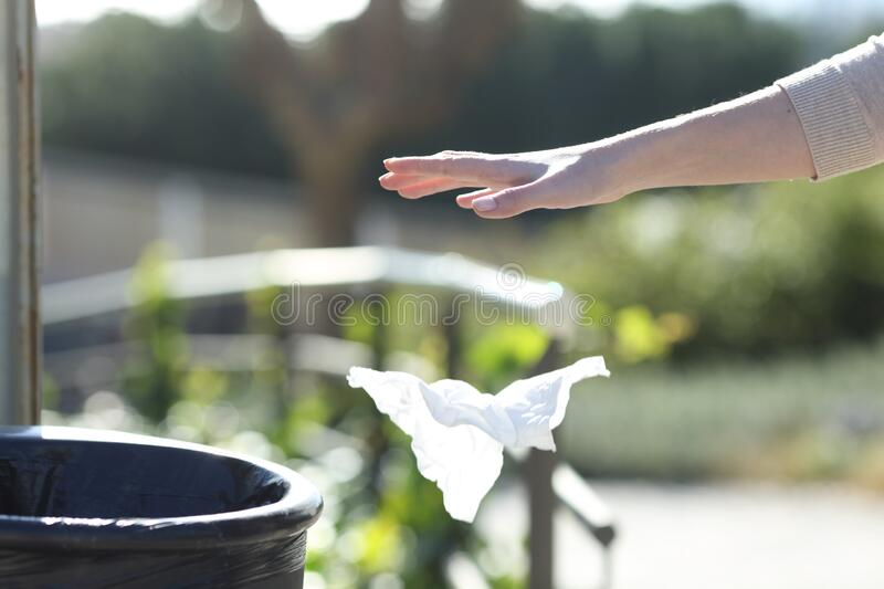Hand throwing litter outside a bin in a park royalty free stock image