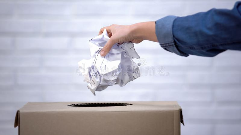 Hand throwing paper into trash bin, waste sorting concept, recycling system. Stock photo stock photos