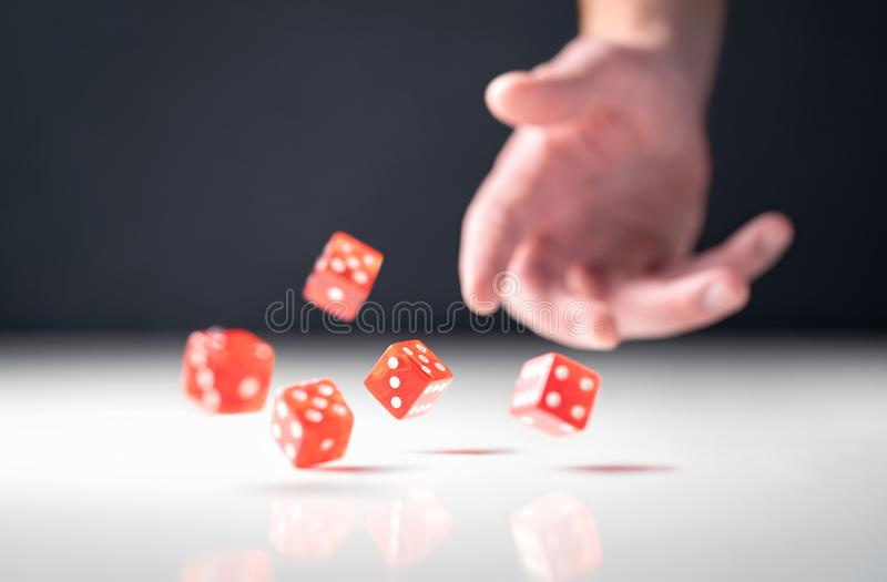 Hand throwing and rolling dice. Gambler tossing five red poker and casino dice on table. Man gambling or playing board game. stock photography