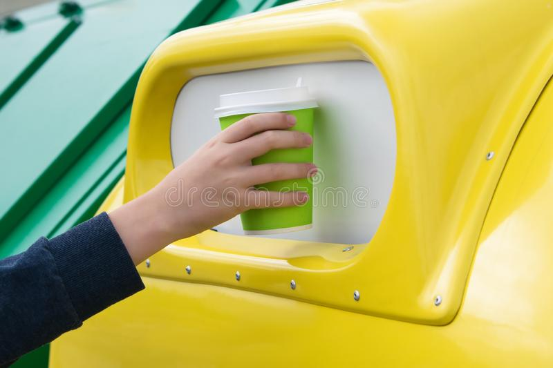 Hand throws paper cup into a yellow trash tank, close-up stock photos